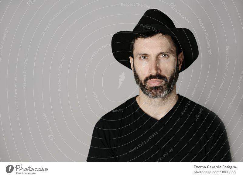 Nahaufnahme eines gut aussehenden bärtigen Mannes mittleren Alters mit Hut vor neutralem Hintergrund Porträt Atelier selbstbewusst grau Vollbart Typ Gesicht