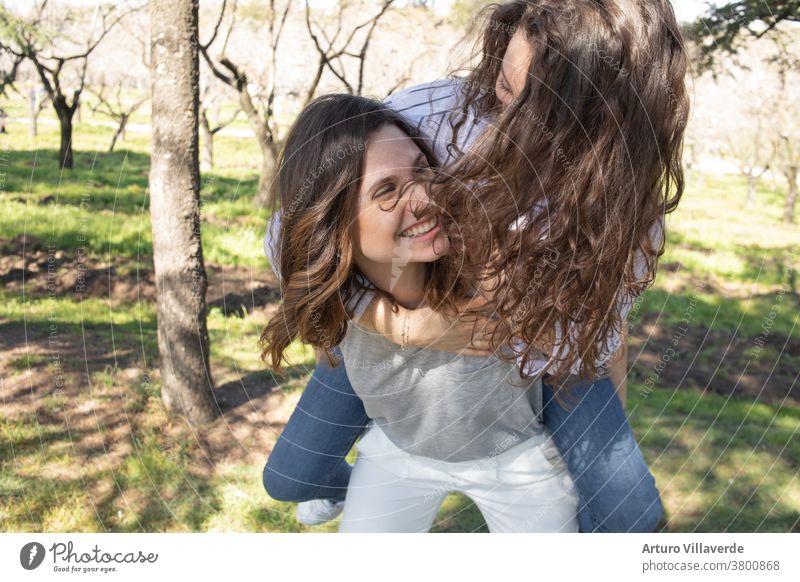 zwei Mädchen einen Park von Mandelbäumen, die zusammen lachend aufeinander kletterten Aktivität Hintergrund schön hell nachlässig heiter farbenfroh Frau Freunde