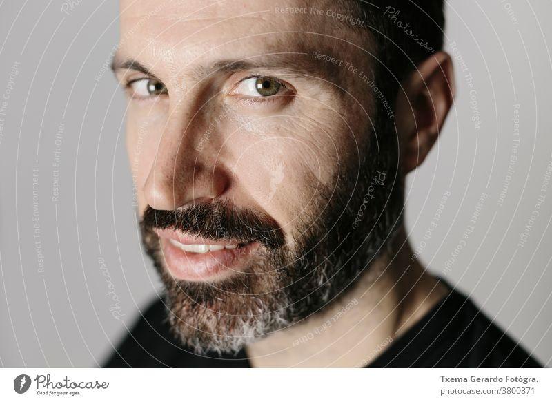 Nahaufnahme eines gut aussehenden bärtigen Mannes mittleren Alters vor neutralem Hintergrund Porträt Atelier selbstbewusst grau Vollbart Typ Gesicht vereinzelt