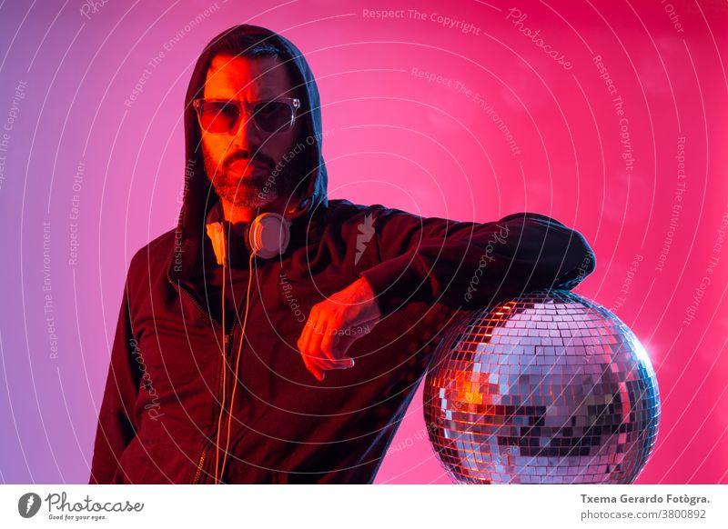 Buntes Studioporträt eines bärtigen DJs mit Kopfhörer und Sonnenbrille vor rotem und blauem Hintergrund. deejay Disco-Musik farbig Pop Klang Discokugel Spiegel