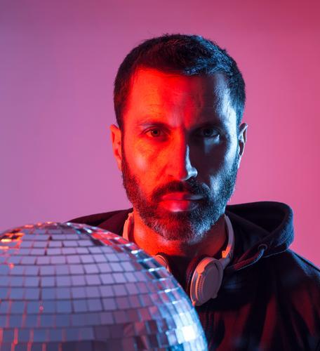 Buntes Studioporträt eines bärtigen DJs mit Kopfhörern vor rot-blauem Hintergrund. deejay Disco-Musik farbig Pop Klang Discokugel Spiegel clubbing farbenfroh