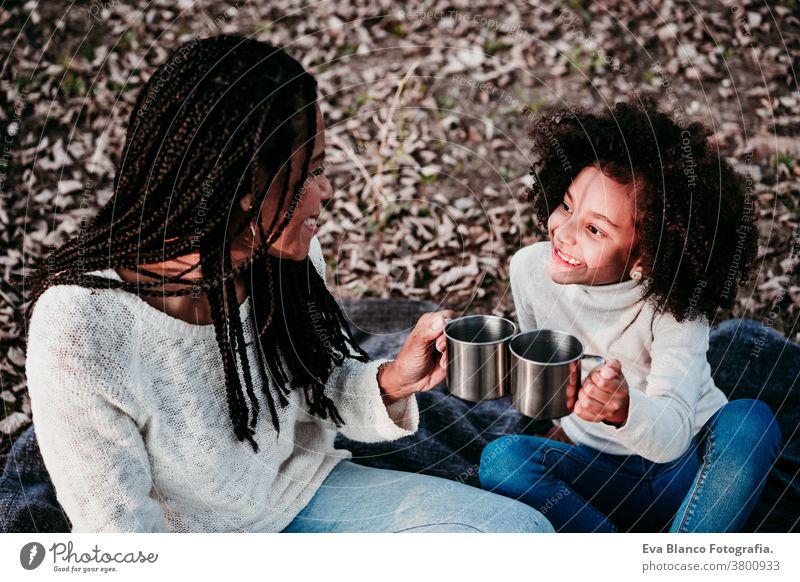 hispanische Mutter und Afrokindermädchen picknicken im Freien und entspannen sich in der Natur. Herbstsaison. Familienkonzept Picknick Porträt Tochter