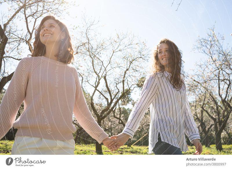 ein paar Mädchen gehen an einem sonnigen Tag Hand in Hand in einem Park spazieren. Sie laufen lächelnd und glücklich umher Aktivität Hintergrund schön hell