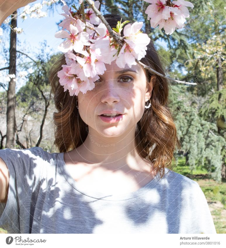 Porträt einer Frau in einem Park mit blühenden Bäumen vor dem Eintritt in den Frühling Erwachsener Aroma attraktiv schön Schönheit Blütezeit brünett Kaukasier