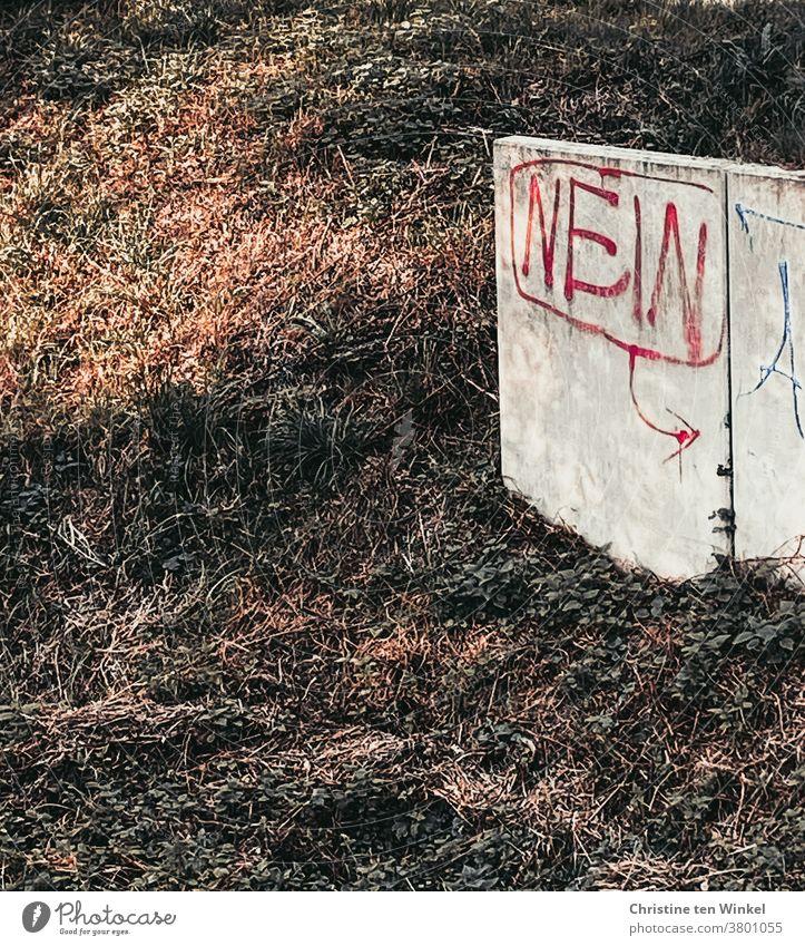 """Das Wort """"NEIN"""" mit roter Farbe geschrieben steht an einer niedrigen hellen Betonwand an einer Böschung Nein Graffiti Wand Mauer Schriftzeichen Fassade"""
