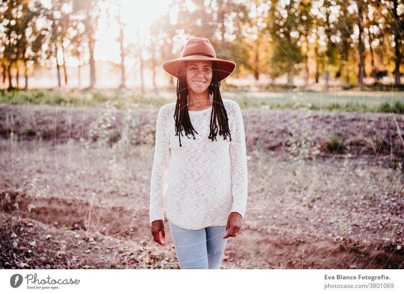 Porträt einer mittel-erwachsenen hispanischen Frau mit Hut bei Sonnenuntergang zur goldenen Stunde, Herbstzeit Afrofrau Latein goldene Stunde Natur im Freien