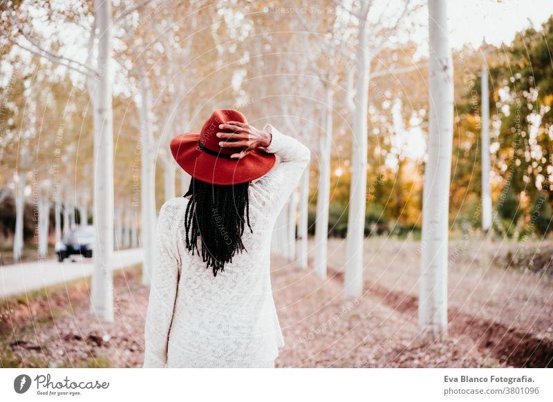 Porträt einer mittel-erwachsenen hispanischen Frau mit Hut bei Sonnenuntergang zur goldenen Stunde, Herbstzeit, schöner Baumpfad im Hintergrund. Afrofrau Latein