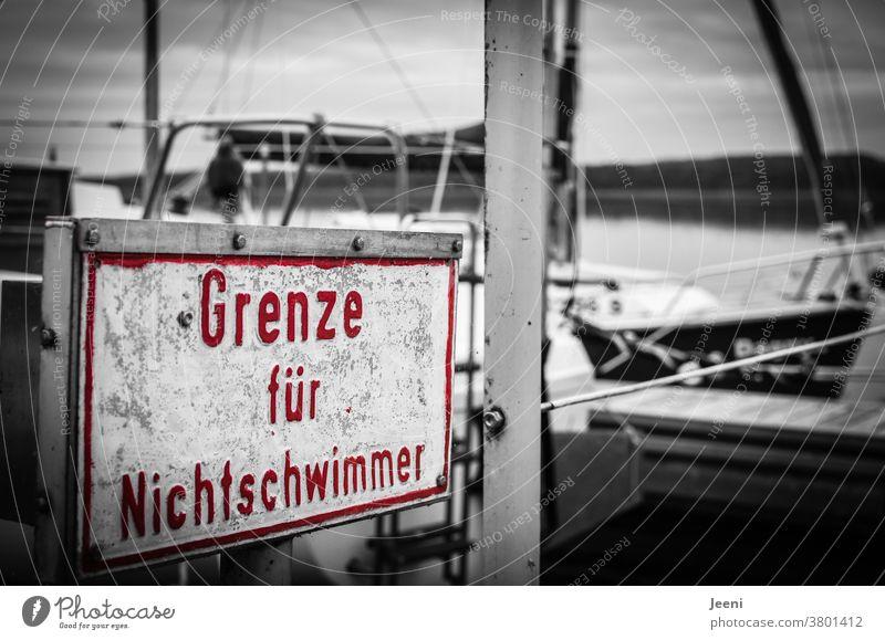 """Auf einem Steg am See steht ein Schild in der Farbe rot mit der Aufschrift """"Grenze für Nichtschwimmer"""" Wasser Rettung ertrinken Erste Hilfe Rettungsschwimmer"""