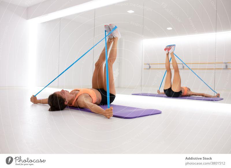 Sportlerin dehnt Beine mit Trainingsband im Fitnessstudio Dehnung elastisch Klebeband Übung Gesunder Lebensstil Wellness Spiegel Frau Reflexion & Spiegelung
