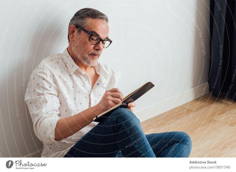 Konzentrierter Mann macht sich Notizen in einem Notizbuch, während er auf dem Boden sitzt schreiben zur Kenntnis nehmen Hinweis Notebook ernst Fokus