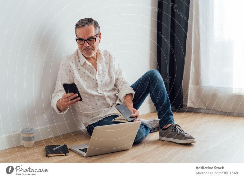 Positiv reifen Mann mit Smartphone und Laptop auf dem Boden Arbeitsbereich benutzend Browsen Fokus positiv Apparatur Gerät zuschauend klug Konzentration Stock