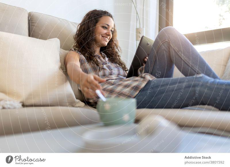 Fröhliche Frau, die im Wohnzimmer auf einem Tablet surft Browsen Tablette sich[Akk] entspannen heimwärts unterhalten benutzend Nachricht heimisch Wochenende