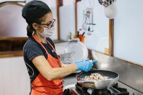 Ein Koch in einem Restaurant, der eine Maske trägt, als Vorsichtsmaßnahme gegen das Coronavirus, das die Mahlzeit zubereitet. Küche Mundschutz covid-19
