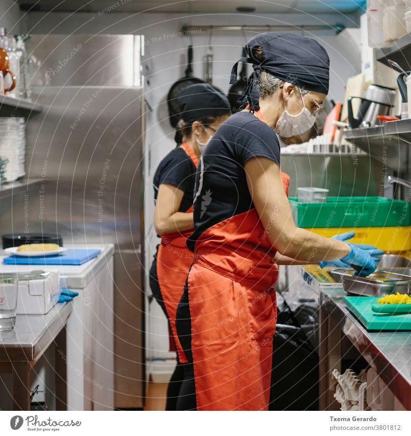 Köche in einem Restaurant, das durch eine Maske geschützt ist, als Vorsichtsmaßnahme gegen das Coronavirus, das Essen zum Mitnehmen zubereitet. Koch Küche