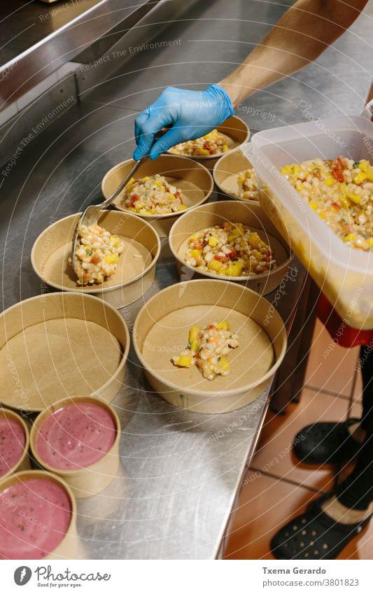 Koch bereitet Reissalate zum Mitnehmen vor. Die verwendeten Behälter sind kompostierbar. Essen zum Mitnehmen Salatbeilage Speiseeis Container Küche Hand Utensil