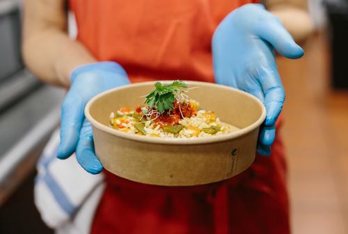 Eine Köchin präsentiert ihren Gourmet-Reissalat in einem kompostierbaren Take-away-Behälter Essen zum Mitnehmen Salatbeilage Koch Vegetarier Veganer Container