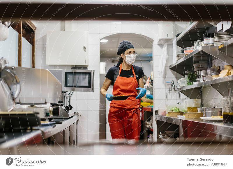 Köche in einem Restaurant, das durch eine Maske geschützt ist, als Vorsichtsmaßnahme gegen das Coronavirus, das Essen zum Mitnehmen zubereitet. Die verwendeten Behälter sind kompostierbar.