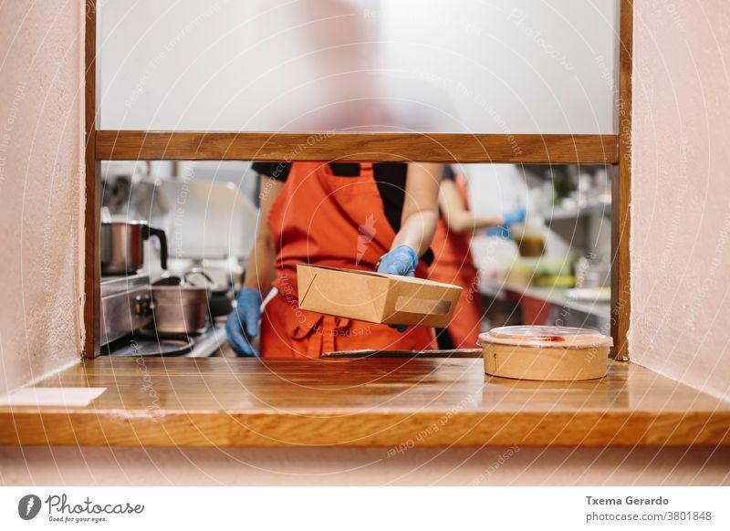 Köche in einem Restaurant, die Essen zum Mitnehmen zubereiten. Die verwendeten Behälter sind kompostierbar. Koch Küche Salatbeilage Fenster Küchenchef Gemüse