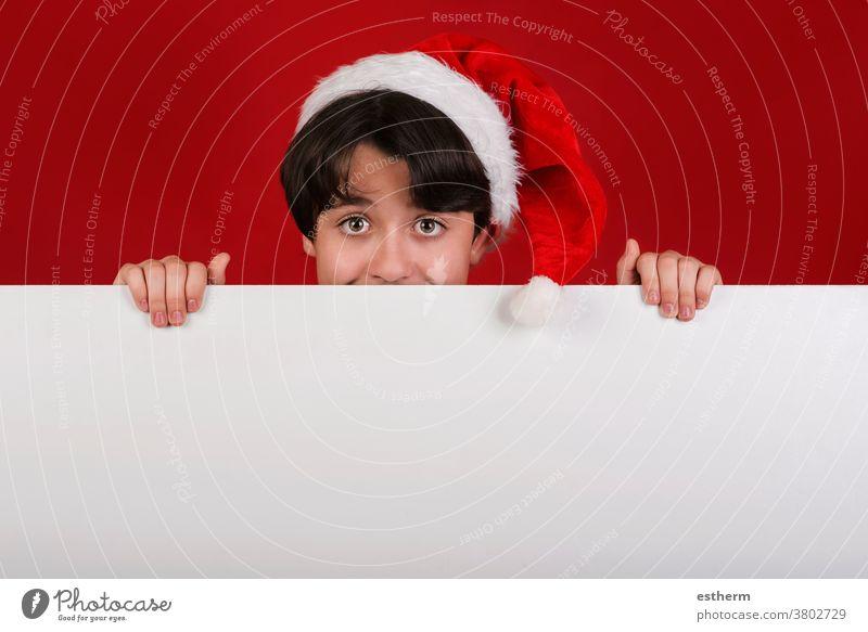 Fröhliche Weihnachten,lächelndes Kind Weihnachtsmann Mütze haltendes leeres Brett x-mas Feier Weihnachtsmütze Inserat Spaß leere Tafel Lächeln Fröhlichkeit