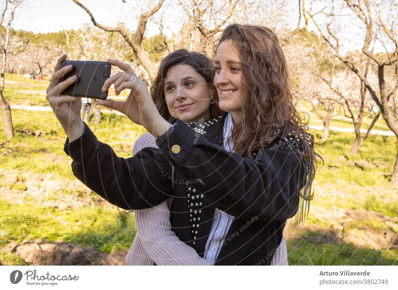 zwei Mädchen in einem Park nehmen beim Umarmen Handyselbstgespräche entgegen. Sie sind beide sehr hübsch und lächeln glücklich. Eine trägt einen rosa Pullover und die andere eine mit Nieten besetzte Jacke.