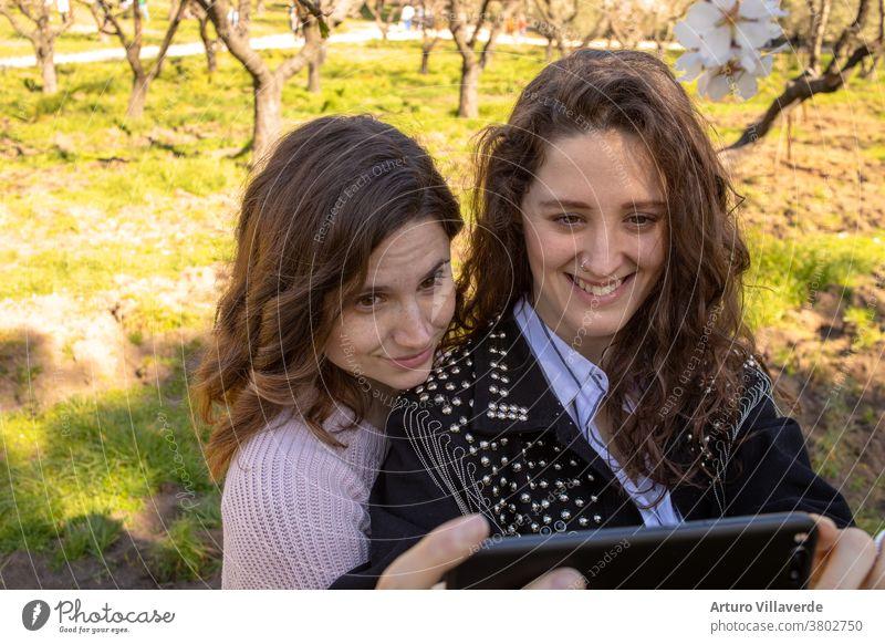 zwei Mädchen in einem Park nehmen mobile Selfs. Sie sind beide sehr hübsch und lächeln glücklich. Eine trägt einen rosa Pullover und die andere eine mit Nieten besetzte Jacke.