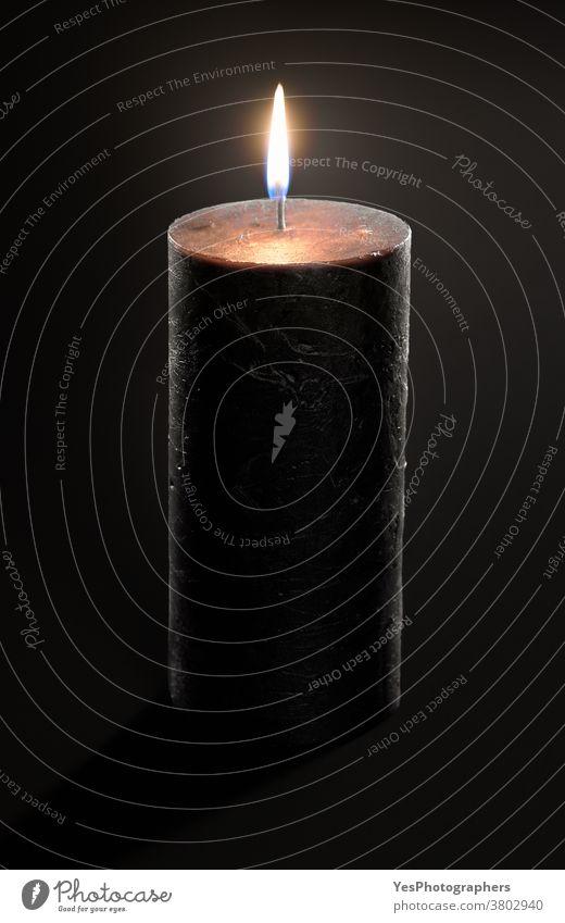 Schwarze Kerze mit einer glühenden Flamme, isoliert auf schwarzem Hintergrund. Abbrennende Kerze Nahaufnahme aromatisch schwarze Kerze Brandwunde Kerzenschein