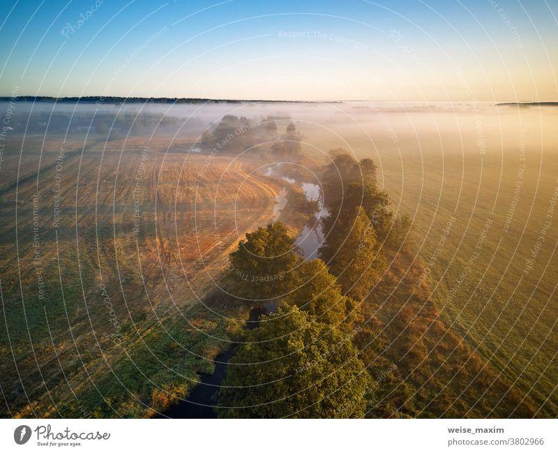 Kleiner Fluss mit Bäumen in Wiese und Feld. Farbenfrohe neblige Morgendämmerung Nebel Natur Herbst Sonnenaufgang Wasser Baum Wald Sonnenlicht Landschaft
