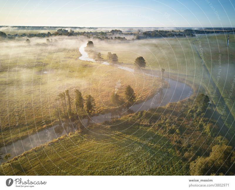 Luftaufnahme des Sonnenaufgangs im Herbst bei Nebel. Kleiner Fluss mit Bäumen in Wiese und Feld Natur Wasser Baum Antenne Wald Morgen Sonnenlicht Landschaft