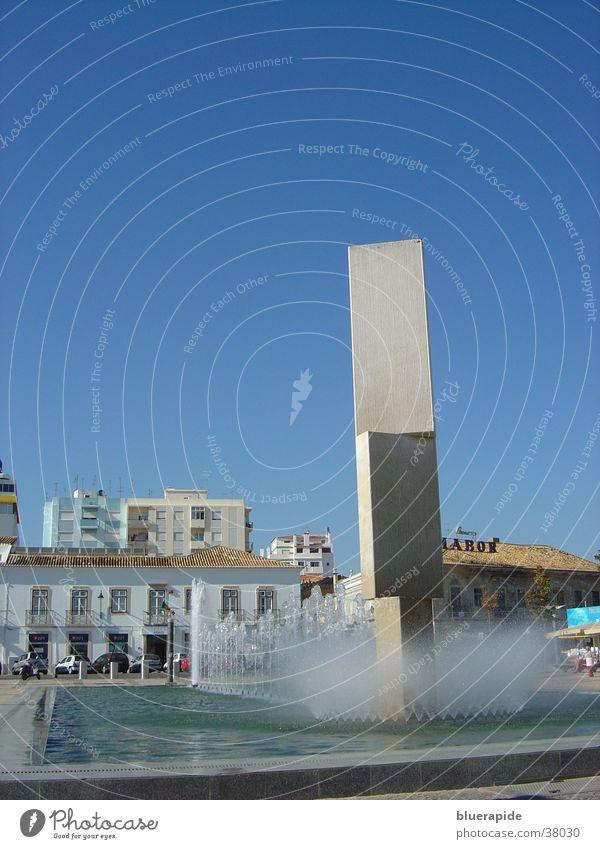 Wie der Himmel so das Wasser? blau Haus Stein Architektur Beton Platz Brunnen Skulptur Becken sprühen Klotz Springbrunnen
