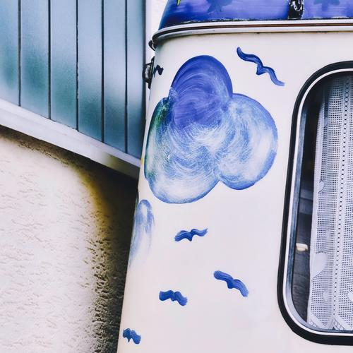 Ausflugsstimmung, blau und nostalgisch: ein alter, schön bemalter Wohnwagen wurde dicht an einer farblich passenden Wand geparkt Wolken Vögel Vorhang Gardine