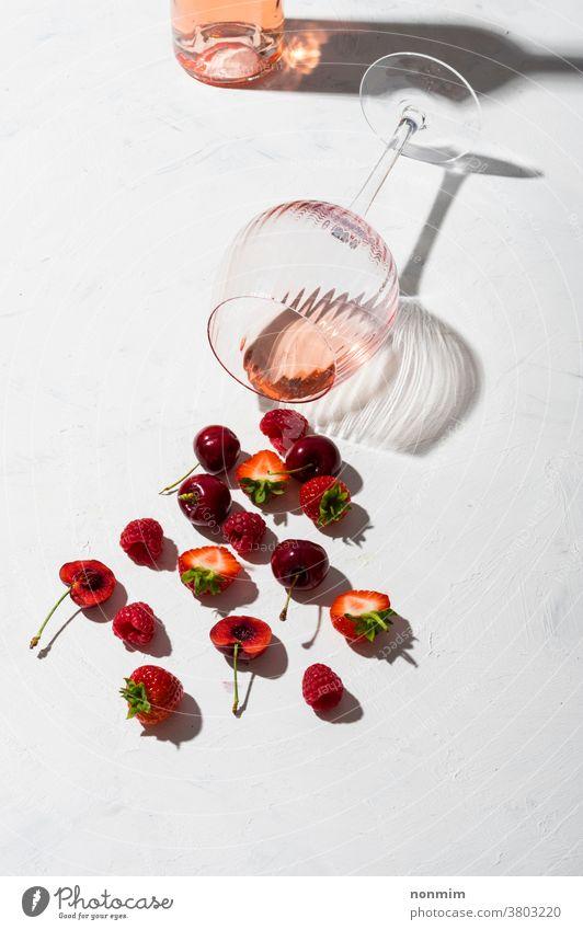 Konzeptkomposition, die Rosenwein-Aromen von Sommerfrüchten von Beeren präsentiert Wein Glas Kelch Zusammensetzung Flachlegung Geschmack Frucht Schatten rot