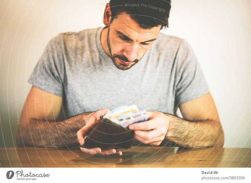 Mann checkt seine Finanzen und zählt Geld aus dem Portemonnaie zählen sparen Zukunftsangst Corona Euro Angst Bargeld
