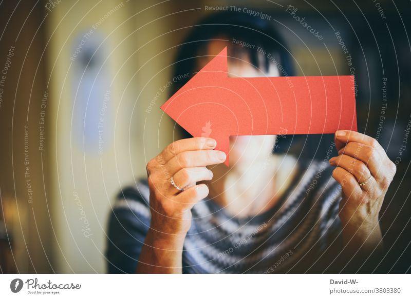 Pfeil in den Händen halten der zurück anzeigt richtungweisend rückwärts Richtungswechsel deuten rot Mensch festhalten