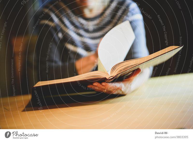 Frau blättert in einem Buch / Album Fotoalbum blättern Hand nachschlagen Buchseite lesen recherchieren Hände Wissen
