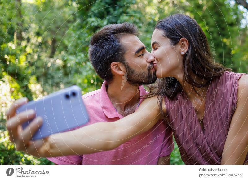 Fröhliches ethnisches Paar nimmt Selfie im Park Kuss Glück Smartphone kuscheln Termin & Datum romantisch Liebe Zusammensein Partnerschaft Apparatur Mobile