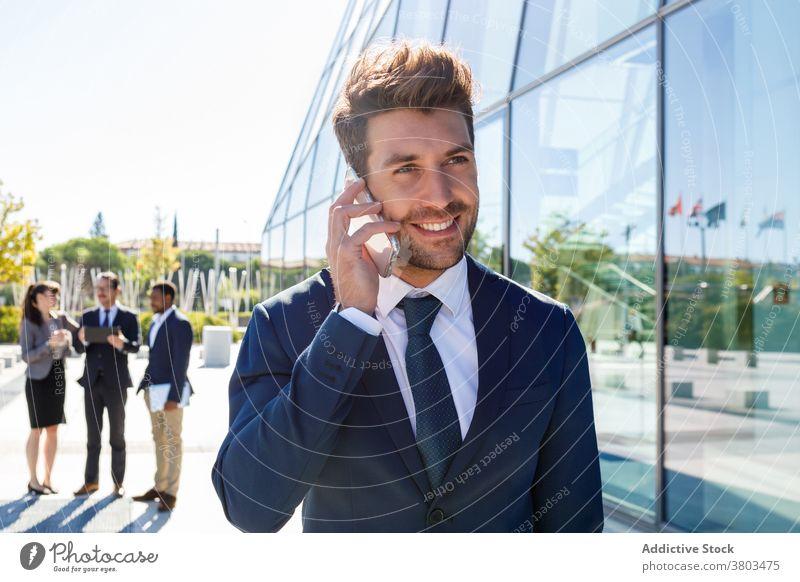 Glücklicher junger Geschäftsmann spricht auf Smartphone auf der Straße Mann reden Gespräch Kommunizieren stilvoll selbstbewusst Unternehmer Anruf Gebäude