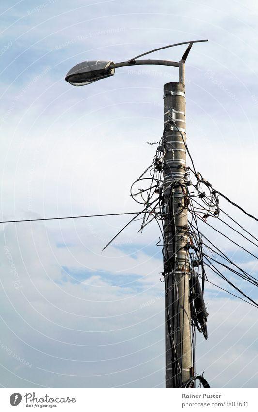 Verschlungene Stromleitungen an einer Straßenlaterne in Rumänien blau Kabel chaotisch Gefahr elektrisch Elektrizität Energie verstrickt Verstrickung Gerät hoch