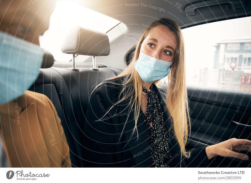 Masken tragendes Geschäftspaar unterhält sich während einer Gesundheitspandemie auf dem Rücksitz eines Taxis Business Geschäftsmann Geschäftsfrau Gesichtsmaske