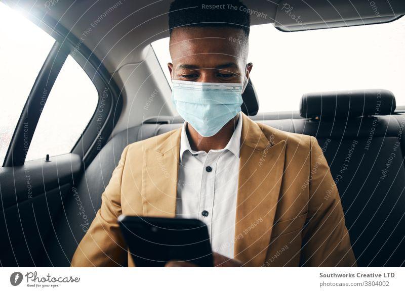 Junger Geschäftsmann mit Maske trägt während Gesundheitspandemie Mobiltelefon auf dem Rücksitz eines Taxis Business Gesichtsmaske Gesichtsbedeckung tragend ppe