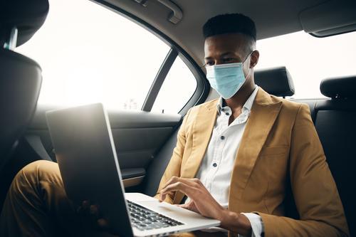 Junger Geschäftsmann mit Maske, der während einer Gesundheitspandemie am Laptop auf dem Rücksitz eines Taxis arbeitet Business Gesichtsmaske Gesichtsbedeckung