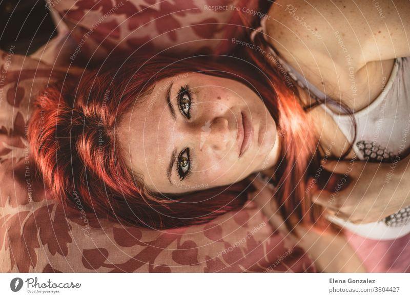 hübsche junge rothaarige Frau mit schönen grünen Augen auf dem Sofa liegend ernst grüne Augen Rotschopf Lügen sinnlich Behaarung Kopf Gesicht brennend Haut