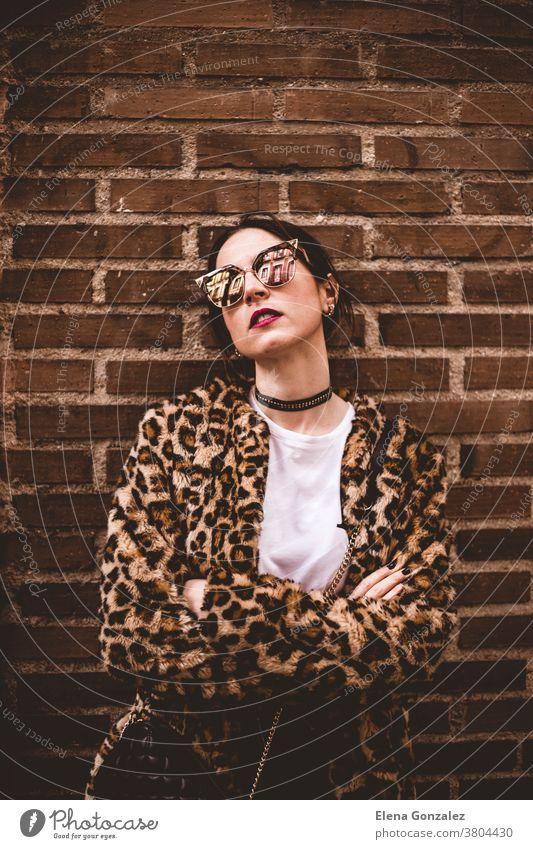 Stilvolles Porträt eines jungen, ernsthaften Modells mit gekreuzten Armen, das einen trendigen Pelzmantel mit Leopartdruck und eine modische Sonnenbrille trägt und auf einem Hintergrund aus rotem Ziegelstein mit Grunge-Wandtextur posiert