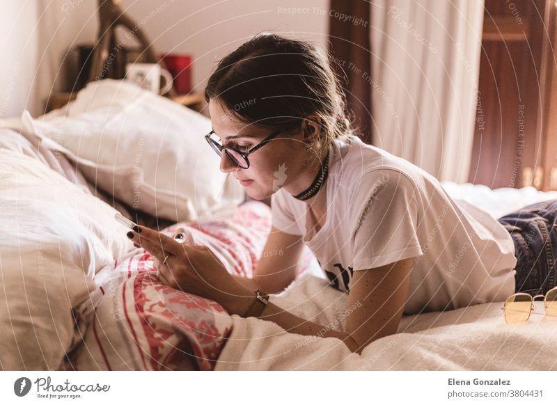Hübsches Mädchen mit Brille liegt im Bett und schaut etwas auf dem Handy Frau jung Mobile Tippen schreibend Lügen Telefon heimwärts Funktelefon Lifestyle