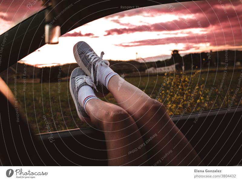 junge Frau mit Turnschuhen, deren Füße bei Sonnenuntergang auf das Autofenster gestützt werden Beine Reise Menschen Lifestyle Sonnenlicht Straße PKW Ausflug