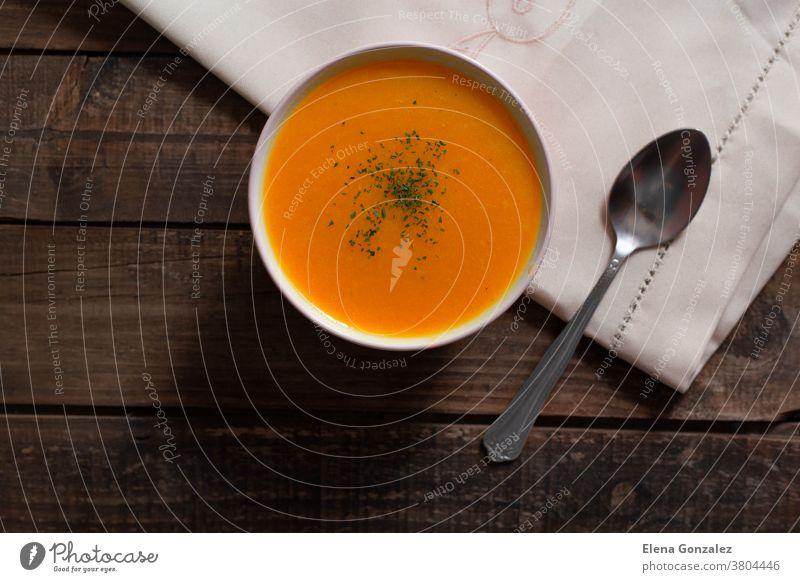 Kürbiscreme mit Schnittlauch und Petersilie auf Holztisch Püree Abendessen Teller Speise Restaurant lecker Bestandteil Erntedankfest Sahne Serviette Thymian