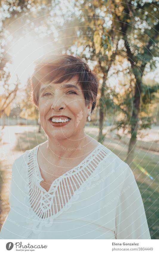 Nahaufnahme des Porträts einer älteren spanischen Frau im Park bei Sonnenuntergang Blick Senior lässig reif mittleres Alter abschließen Freizeit lieblich 50s