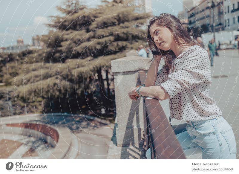 Hübsche junge Frau ruht auf einem Geländer in der Nähe des Königspalastes von Madrid, Spanien königlicher Palast Tourist Mädchen Mode modisch Tasche Handtasche