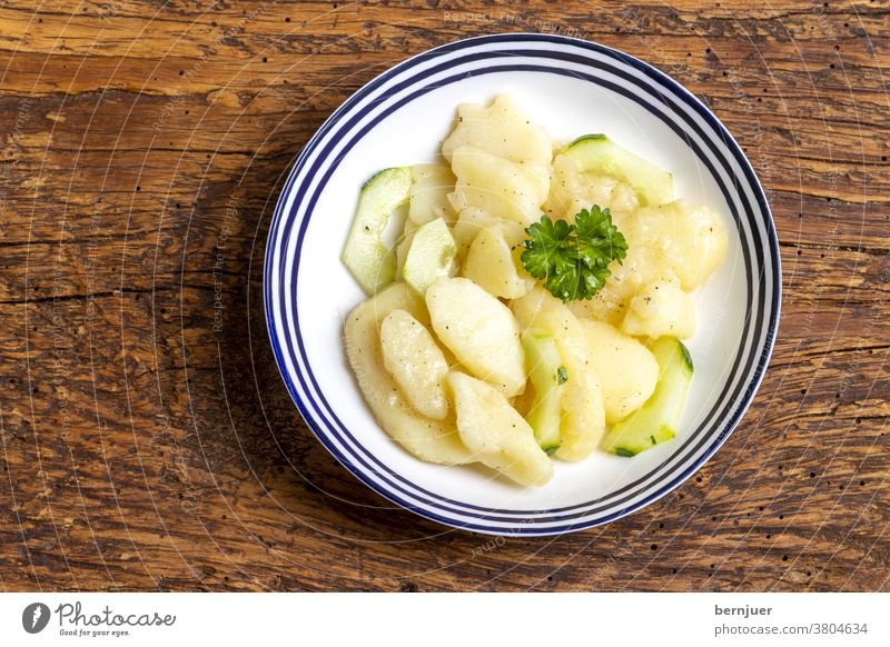 bayerischer Kartoffelsalat Salat Aufsicht Holz rustikal Petersilie Bayern essig öl frisch Essen grün Dressing Gemüse Zwiebel Schüssel Gewürze Vorspeise Gericht