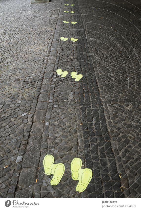 Mindestabstand von 1,5 Meter durch Schuhabdruck Bodenmarkierung mindestens pandemie hinweisend sicherheitsabstand Bodenansicht Abstand Kopfsteinpflaster