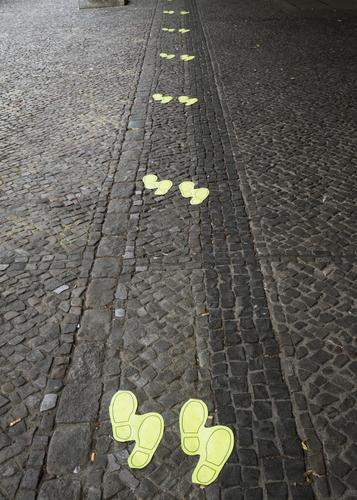 Mindestabstand von 1,5 Meter durch Schuhabdruck Bodenmarkierung mindestens sicherheitsabstand Abstand Kopfsteinpflaster Abstand halten Warteschlange Hinweis